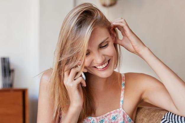 Gelukkig jonge vrouw geniet van vrije tijd thuis, heeft telefoongesprek met beste vriend, binnenlandse problemen bespreken en positief nieuws delen, zit op een comfortabele bank in de kamer.