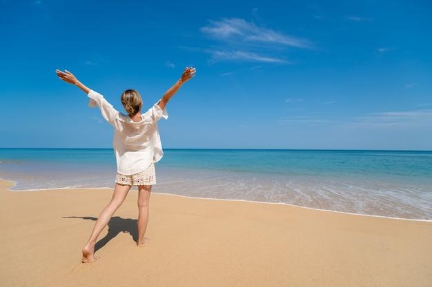 Gelukkig jonge vrouw genieten van vrijheid met open handen op zee.