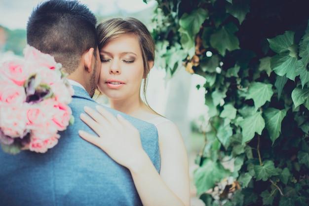 Gelukkig jonge vrouw haar man knuffelen op hun trouwdag in een park. concept van huwelijk en liefde.