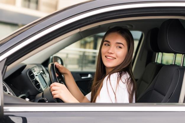 Gelukkig jonge vrouw haar nieuwe auto rijden