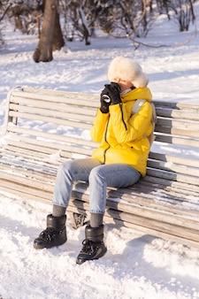 Gelukkig jonge vrouw in de winter in warme kleren in een besneeuwd park op een zonnige dag zit op de banken en geniet van de frisse lucht en de koffie alleen