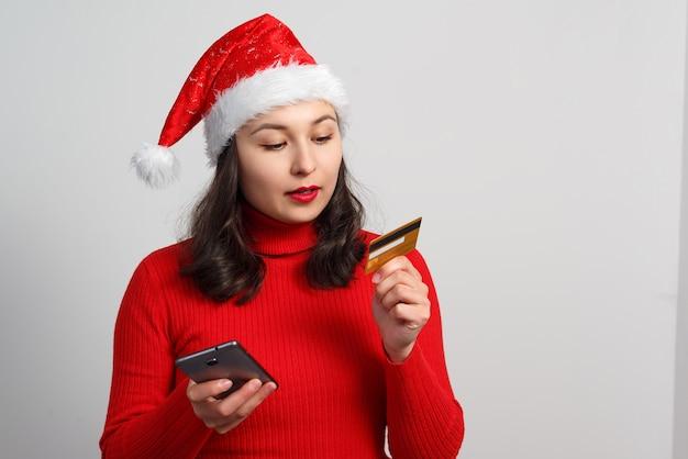 Gelukkig jonge vrouw in een kerst-pet en een rode trui houdt een smartphone en een creditcard op wit.