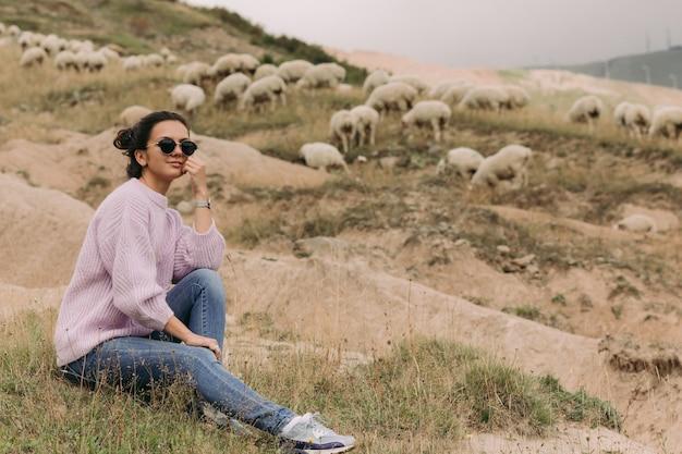 Gelukkig jonge vrouw in een trui tegen kuddes schapen in de bergen