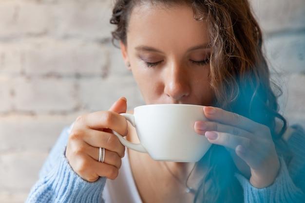 Gelukkig jonge vrouw in gebreide warme trui met handen een kopje gezonde warme blauwe koffie latte. blauwe koffie latte gemaakt met verse koffiebonen en bluechai vlindererwt thee. welzijn concept.