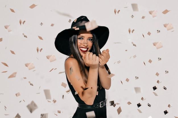 Gelukkig jonge vrouw in heks halloween kostuum met hoed en zwarte jurk permanent en lachend over witte muur met confetti. halloween feest