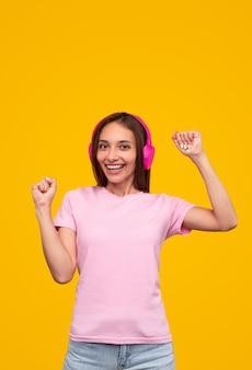 Gelukkig jonge vrouw in stijlvolle kleding glimlachend voor camera en dansen terwijl u luistert naar muziek tegen gele achtergrond