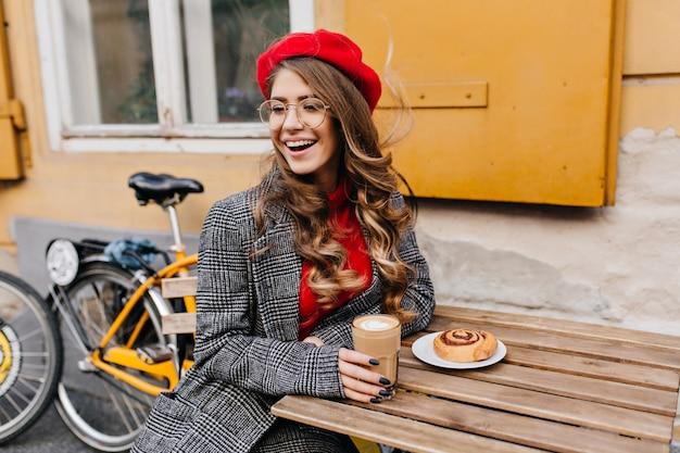 Gelukkig jonge vrouw in tweed jas zitten op terras met glas cappuccino