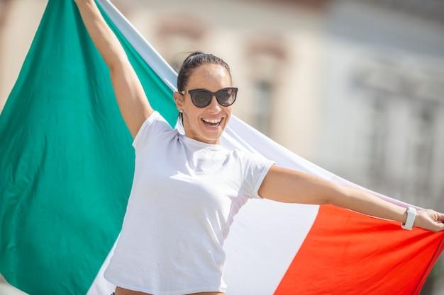 Gelukkig jonge vrouw in zonnebril en wit t-shirt houdt de vlag van italië buitenshuis.