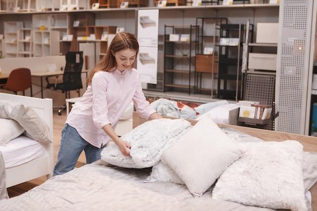 Gelukkig jonge vrouw kussens kiezen om te kopen bij meubelwinkel