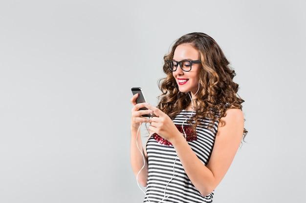 Gelukkig jonge vrouw luisteren muziek met een koptelefoon. geïsoleerd portret op grijze muur