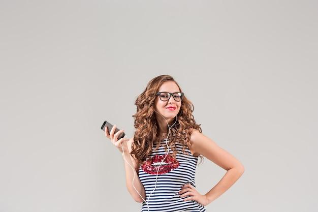 Gelukkig jonge vrouw luisteren muziek met koptelefoon op grijs