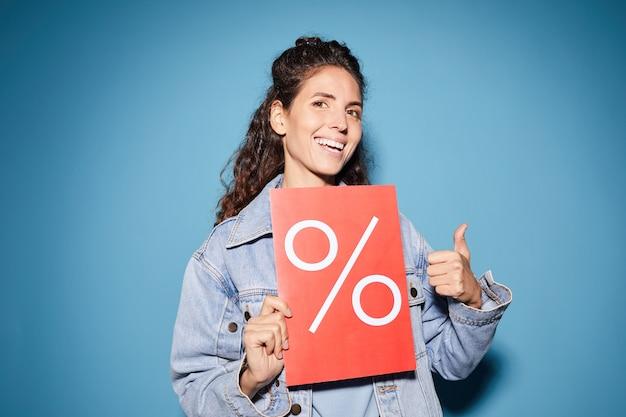 Gelukkig jonge vrouw met aanplakbiljet met procentteken en duim opdagen tegen de blauwe achtergrond