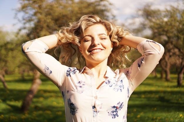 Gelukkig jonge vrouw met blond haar, gekleed in een jurk, buiten poseren in een tuin met kersenbomen in de zon, glimlachend. krullen die fladderen in de wind