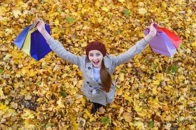 Gelukkig jonge vrouw met boodschappentassen in de hand in herfst park. consumentenconcept. bovenaanzicht.