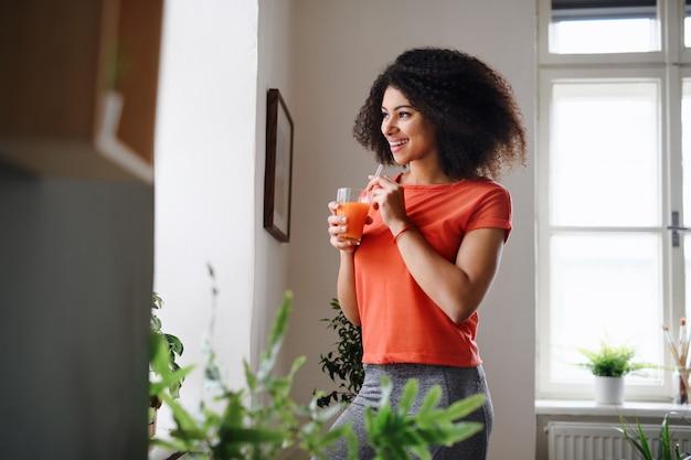 Gelukkig jonge vrouw met drankje binnenshuis thuis, oefening doen. sportconcept.