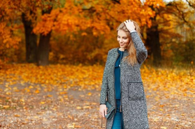Gelukkig jonge vrouw met een glimlach in modieuze herfstkleren poseren in de buurt van bomen met geel gebladerte