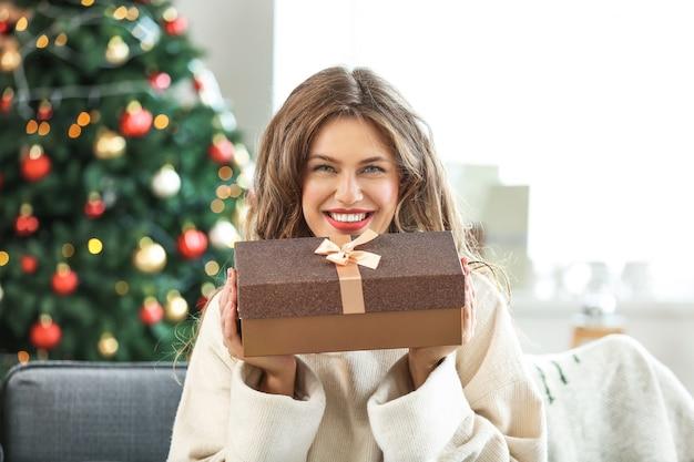 Gelukkig jonge vrouw met kerstcadeau thuis
