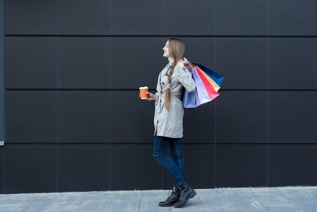Gelukkig jonge vrouw met kleurrijke tassen en papieren beker op straat. b
