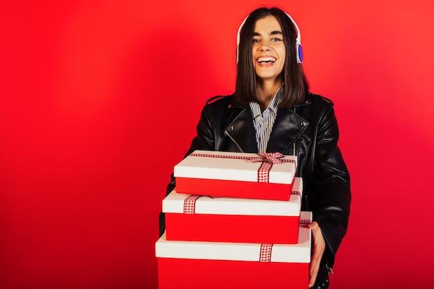 Gelukkig jonge vrouw met koptelefoon met geschenken in haar handen op een rode achtergrond met kopie ruimte.
