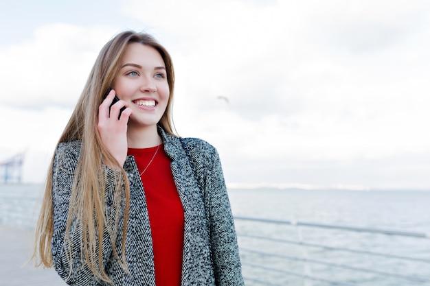 Gelukkig jonge vrouw met lang lichtbruin haar en prachtige glimlach praten over smartphone met prachtige glimlach in de buurt van de zee