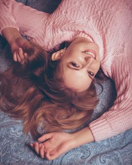 Gelukkig jonge vrouw met rood haar in een roze trui liggend op het bed