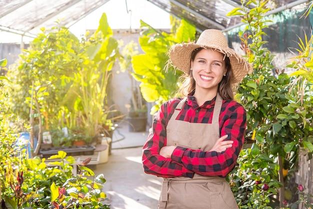 Gelukkig jonge vrouw met schort en strooien hoed in haar kas. duurzaam groen bedrijfsconcept