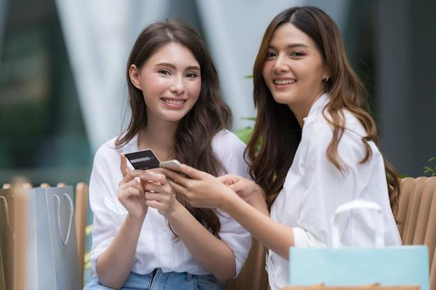 Gelukkig jonge vrouw met smileygezicht praten en lachen bedrijf creditcard en met behulp van telefoon
