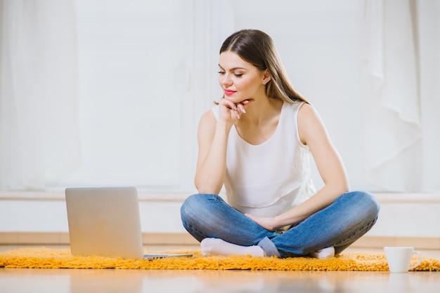 Gelukkig jonge vrouw of student met laptop zittend op de vloer thuis