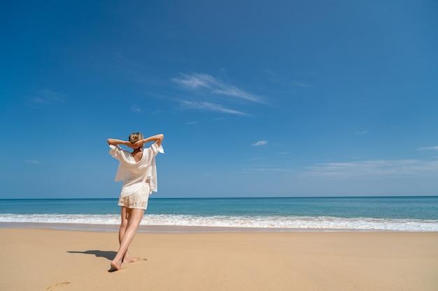 Gelukkig jonge vrouw ontspannen op het strand, armen opgewekt tot aan de hemel.