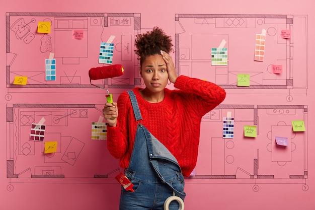 Gelukkig jonge vrouw ontwerper planning renovatie van modern appartement