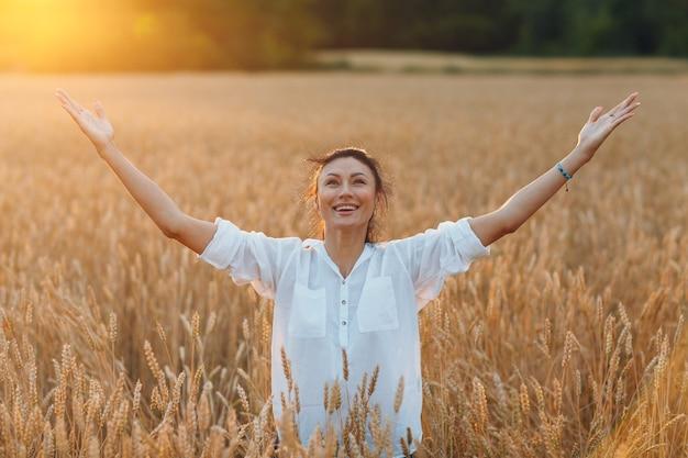 Gelukkig jonge vrouw op tarweveld met opgeheven handen genieten van vrijheid, herfst oogst concept.