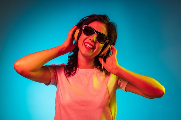 Gelukkig jonge vrouw permanent en glimlachend in zonnebril over trendy blauwe neon studio