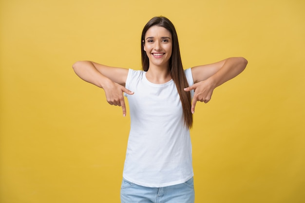 Gelukkig jonge vrouw permanent en wijzende vinger op kopie ruimte geïsoleerd over geel gouden muur achtergrond op zoek camera.