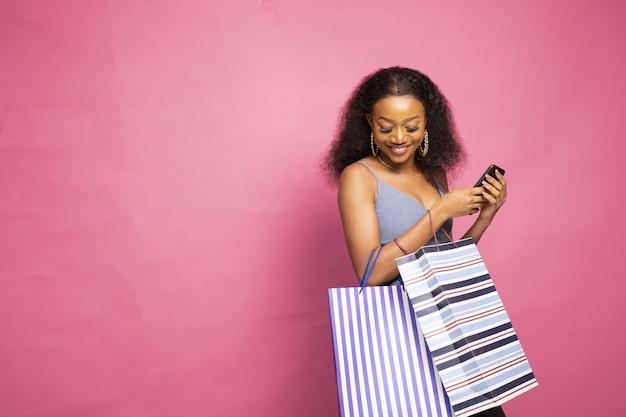 Gelukkig jonge vrouw poseren met boodschappentassen geïsoleerd op een roze muur