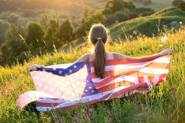 Gelukkig jonge vrouw poseren met de nationale vlag van de v.s. staande buiten bij zonsondergang. positief meisje dat de onafhankelijkheidsdag van de verenigde staten viert. internationale dag van democratie concept.