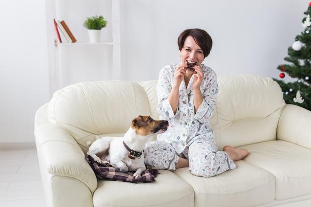 Gelukkig jonge vrouw pyjama dragen in de woonkamer met kerstboom