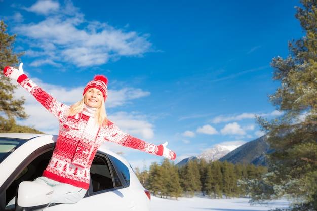 Gelukkig jonge vrouw reizen met de auto op wintervakantie. gezond actief levensstijlconcept