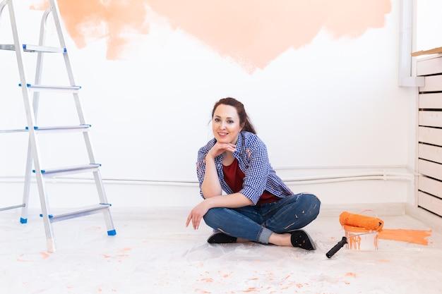 Gelukkig jonge vrouw schilderij binnenmuur met verfroller in nieuw huis