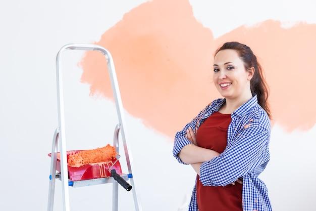 Gelukkig jonge vrouw schilderij muur in haar nieuwe appartement. renovatie-, herinrichting- en reparatieconcept.