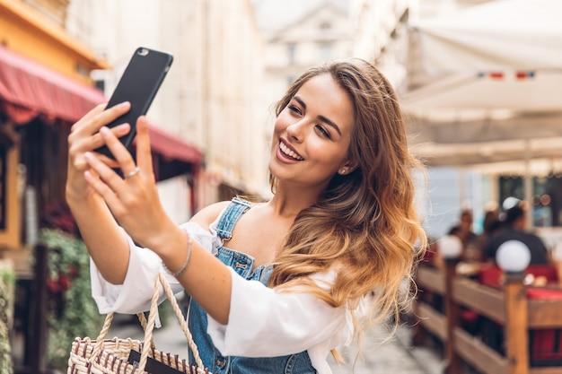 Gelukkig jonge vrouw selfie te nemen. vrouw die selfie foto met een smarphone in de stad nemen