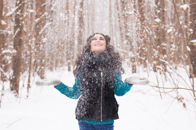 Gelukkig jonge vrouw speelt met een sneeuw op besneeuwde bossen buiten