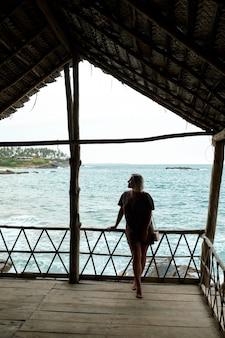 Gelukkig jonge vrouw staan op bungalow balkon