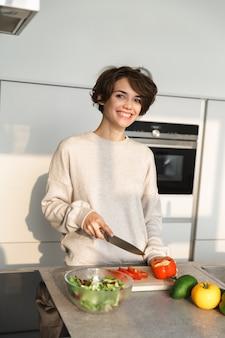 Gelukkig jonge vrouw verse salade koken in de keuken thuis