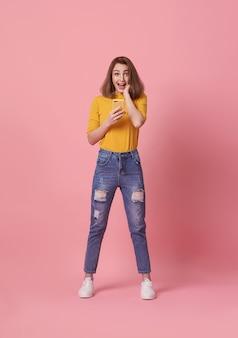 Gelukkig jonge vrouw vieren met mobiele telefoon geïsoleerd op roze achtergrond.