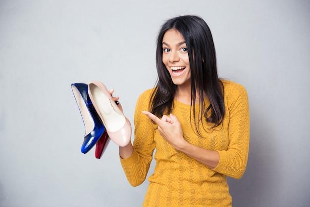 Gelukkig jonge vrouw wijzende vinger op schoenen
