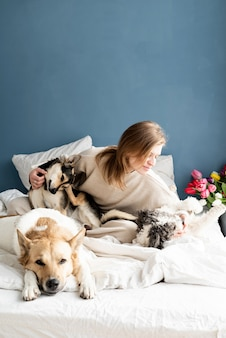 Gelukkig jonge vrouw zittend in het bed met haar honden, blauwe muur achtergrond