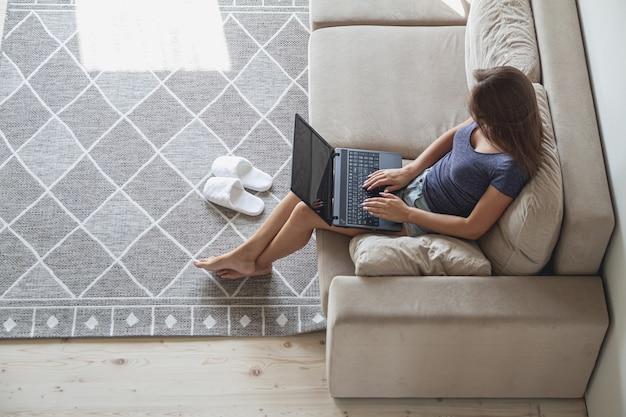 Gelukkig jonge vrouw zittend op de bank en met behulp van laptop thuis