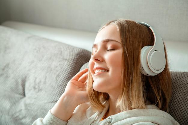 Gelukkig jonge vrouw zittend op de bank in koptelefoon. vrouw of tienermeisje rusten, gelukzaligheid geniet van het luisteren naar muziek op de bank in het interieur van de woonkamer. portret van een vrouw die met gesloten ogen rust.