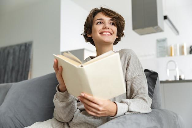 Gelukkig jonge vrouw zittend op een bank thuis, een boek lezen