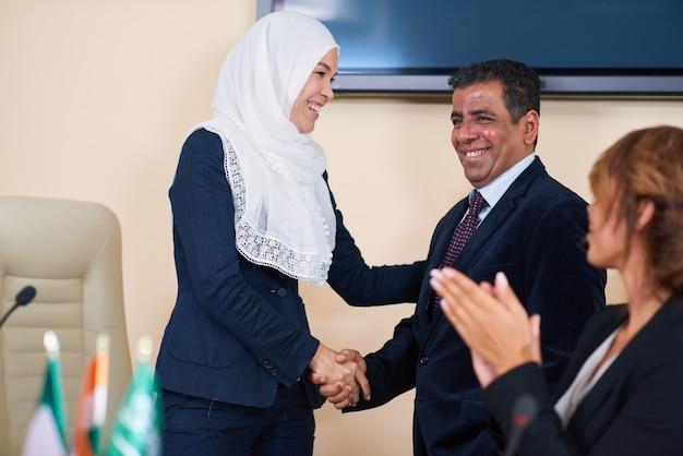 Gelukkig jonge vrouwelijke afgevaardigde in hijab feliciteren met een van de buitenlandse sprekers na zijn verslag op conferentie of top